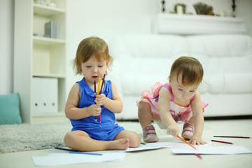 Two little cute girls paint pencils on floor in room at home.