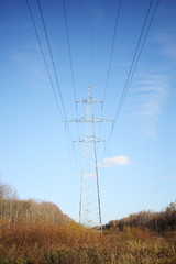 Power lines with long wires at background of blue sky