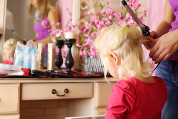 Back of pretty blonde little girl and hands of hairdresser