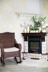 Wicker rocking chair and fireplace with candles and flowers