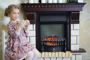 Little cute girl with straw balls sits on chair near fireplace