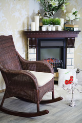 Wicker rocking chair, candlestick and fireplace with candles