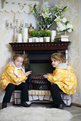 Two little girls in same clothes sits near fireplace