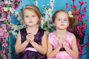 Two cute little girls in dresses sit with folded hands in prayer