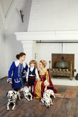 Young father, mother in medieval costumes look at little son