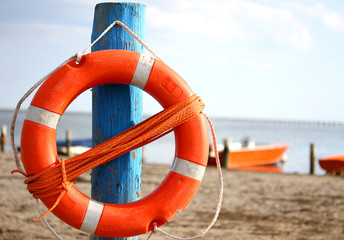pole with lifejacket at sea on the beach by the sea