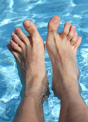 man's feet on the bathtub of a relaxing pool