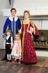 Father, mother, little daughter and son in medieval costumes