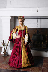 Pretty woman in red medieval costume stands near fireplace