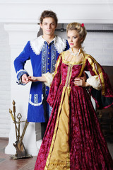 Young couple in colored medieval costumes stand