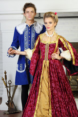 Young man and pretty woman in medieval costumes stand