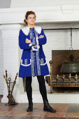 Young man in medieval blue caftan stand next to fireplace.