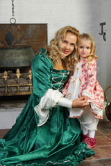 Beautiful woman in green medieval costume with her daughter