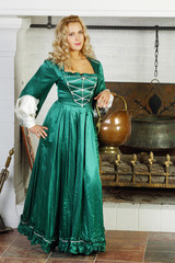 Pretty woman in green medieval costume with pot on hand stands