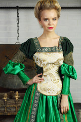 Beautiful woman in green medieval costume stands