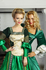 Two beautiful women in green medieval costumes stand