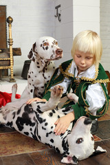 Cute blonde little boy in medieval costume plays with dogs