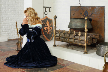 Young woman in medieval costume prays near fireplace with boiler