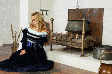 Cute woman in medieval costume prays near fireplace with boiler.