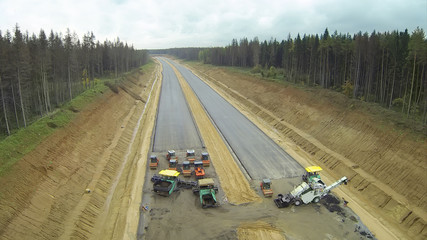 Machines on road construction among forest.