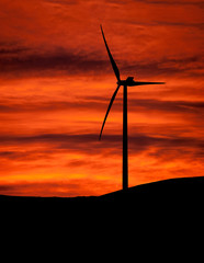 Sunset wind turbine on hill. Clean energy.