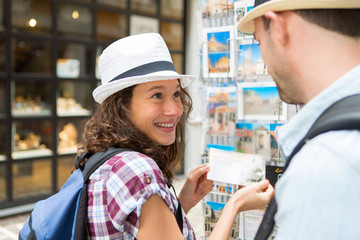 Young happy couple choosing postcards during holidays