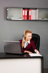 beautiful, happy businesswoman typing on laptop at her desk