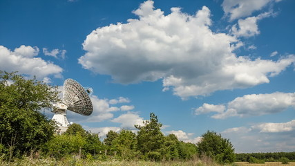 The parabolic antenna on a background of the blue sky