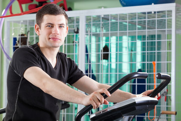 Young man cycling on stationary bike