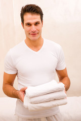 Young man holding stack of fresh towels