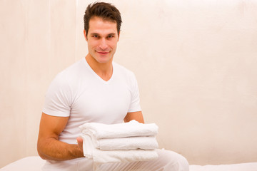 Smiling young man holding stack of towels
