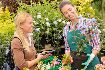 Garden centre woman worker selling potted plant