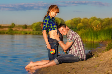 Happy and young pregnant couple having fun on the beach. Summer