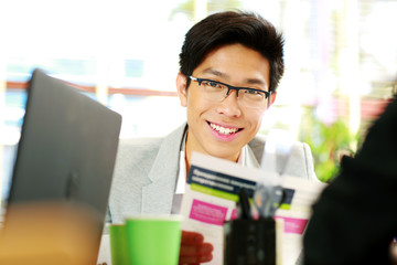 Asian businessman in glasses sitting at the table in office