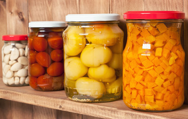 Preserved  vegetable on shelf near a brown wooden wall