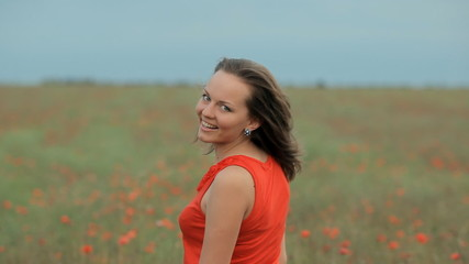 Young smiling beautiful girl in poppy field