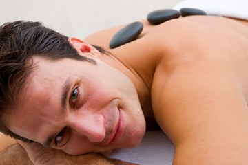 Smiling young man receiving hot stone treatment