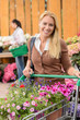 Woman buying flowers shopping cart garden center