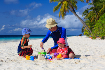Father and kids making sand castle at tropical beach