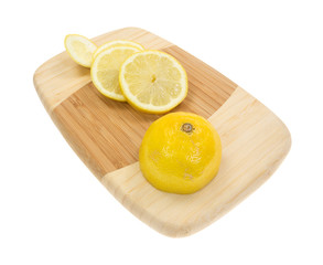 Lemon with slices on wood cutting board