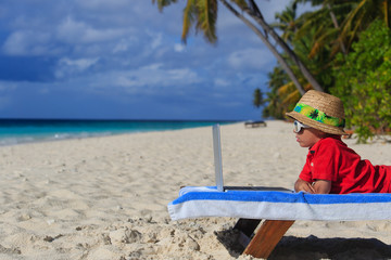 little boy with laptop at the beach