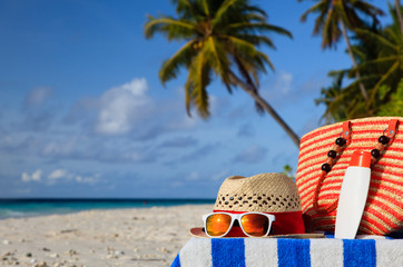 hat, bag, sun glasses on tropical beach