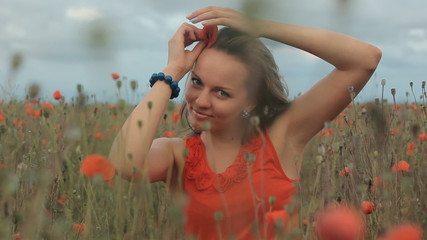 Beautiful smiling happy young girl sitting in poppy field with a