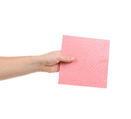 Hand holding pink cleaning sponge.