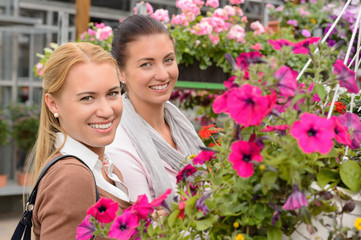 Two woman in garden center colorful flowers