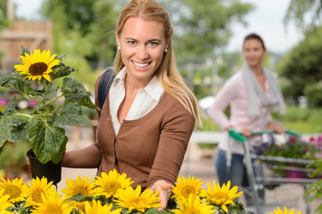 Smiling woman hold potted sunflower garden center
