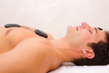 Young man enjoying a hot stone massage