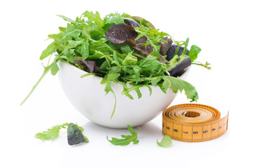 bowl of fresh lettuce and measuring tape, isolated