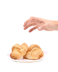 Hand trying to grab croissants.