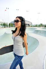young woman skateboarder walking at skatepark